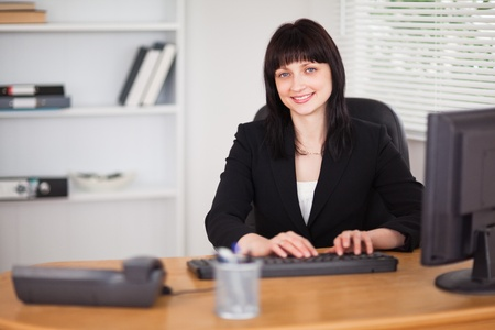 Pretty brunette woman working on a computer while sitting at a desk in the office photo