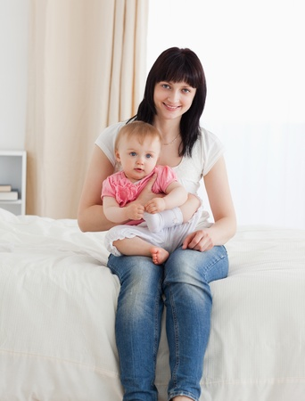 Beautiful brunette woman holding her baby on her knees while sitting on a bed in her appartment Stock Photo - 10070999
