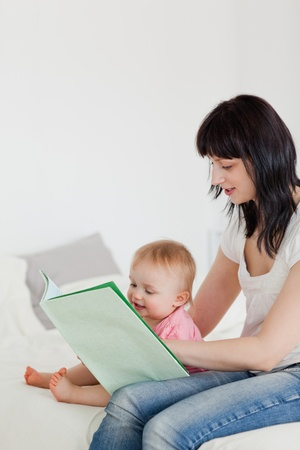 Cute brunette woman showing a book to her baby while sitting on a bed in her apartment photo