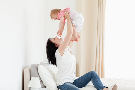 Charming brunette woman playing with her baby while sitting on a bed in her appartment photo