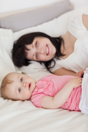Attractive brunette female posing with her baby while lying on a bed in her apartment photo