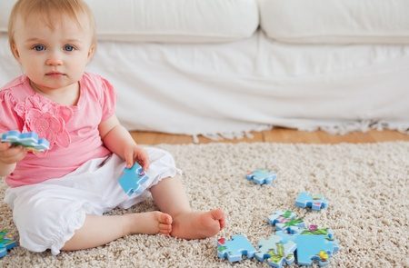 Lovely baby playing with puzzle pieces while sitting on a carpet in the living room photo
