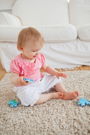 Baby playing with puzzle pieces while sitting on a carpet in the living room photo