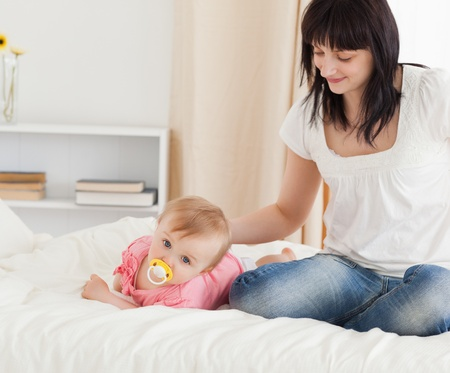 Cute brunette woman looking at her lying baby on a bed in her appartment photo