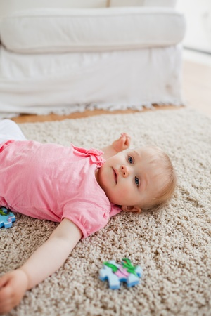 Lovely blond baby playing with puzzle pieces while lying on a carpet in the living room photo