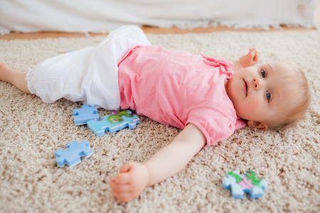 Cute blond baby playing with puzzle pieces while lying on a carpet in the living room photo