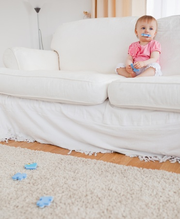 Cute blond baby playing with puzzle pieces while sitting on a sofa in the living room photo