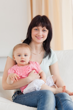 Charming woman holding her baby in her arms while sitting on a sofa in the living room Stock Photo - 10073234