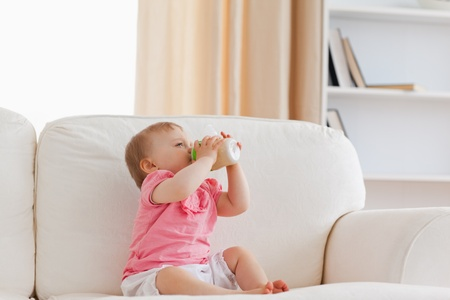 Cute blond baby bottle-feeding while sitting on a sofa in the living room photo