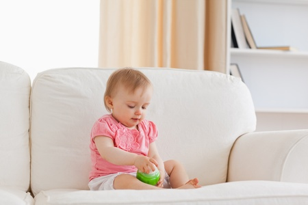 Cute blond baby playing with a ball while sitting on a sofa in the living room photo