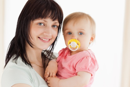 Attractive woman holding her baby in her arms while standing in the living room Stock Photo - 10069725