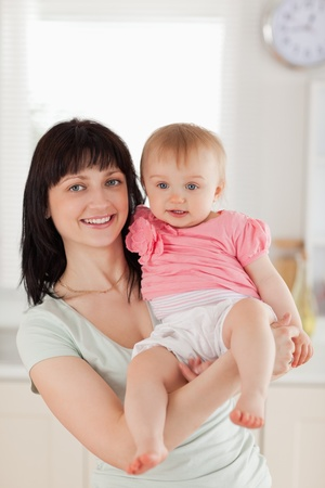 Attractive woman holding her baby in her arms while standing in the kitchen photo