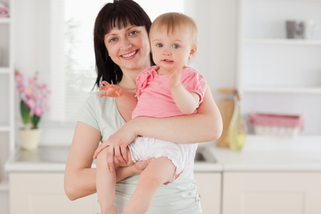 Charming woman holding her baby in her arms while standing in the kitchen photo