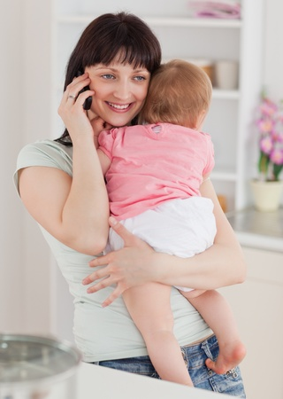 Lovely woman on the phone while holding her baby in her arms in the kitchen Stock Photo - 10070351