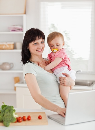 Cute woman holding her baby in her arms while standing in the kitchen photo