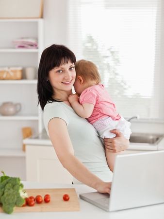 Good looking brunette woman holding her baby in her arms while standing in the kitchen photo