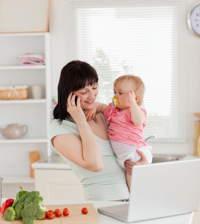 Attractive brunette woman on the phone while holding her baby in her arms in the kitchen photo
