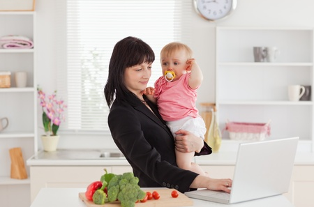 Beautiful brunette woman in suit holding her baby in her arms while working with her laptop in the kitchen photo