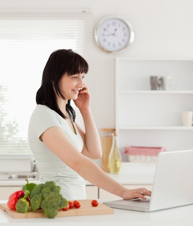 Attractive brunette woman on the phone while relaxing with her laptop in the kitchen photo