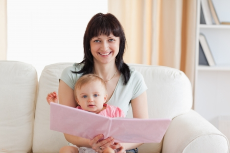 Good looking woman holding her baby and a book in her arms while sitting on a sofa in the living room photo