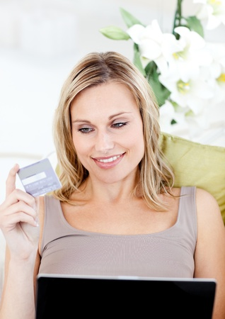 Delighted woman holding a card and a laptop Stock Photo - 10074844