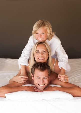 Happy family having fun together lying on bed Stock Photo - 10075079
