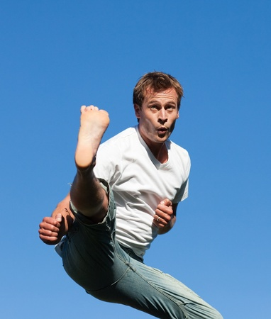 Smiling Man jumping in the air outdoor photo