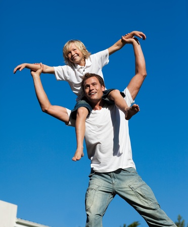Young father with his son on his back outdoor photo