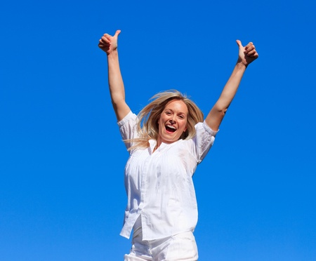 Portrait of an delighted woman jumping in the air outdoor  photo