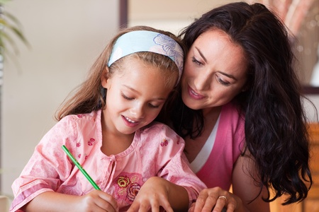 Brunette mother with blond daughter painting together photo