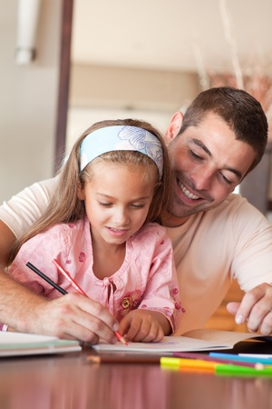 Concentrated girl painting with her father photo
