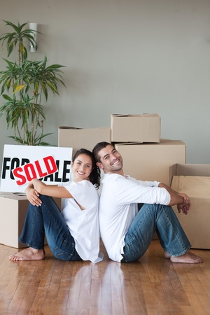 Cheerful couple sitting on the floor Stock Photo - 10075119