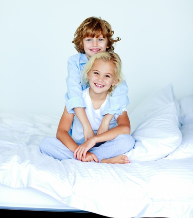 Brother embracing his sister in bed  photo