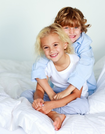 Little girl and boy on the bed photo