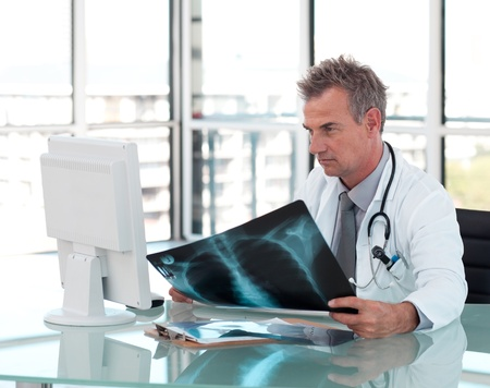 Pensive male doctor looking on his computer