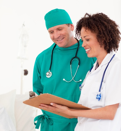 Bright medical team holding a clip board photo