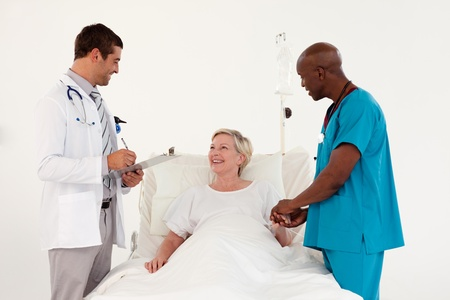 Smiling patient between a male doctor and surgeon Stock Photo - 10074809