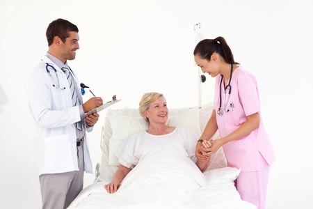 Smiling patient lying between friendly nurse and doctor photo