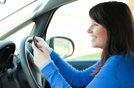 Smiling teen girl using a mobile phone while driving  photo