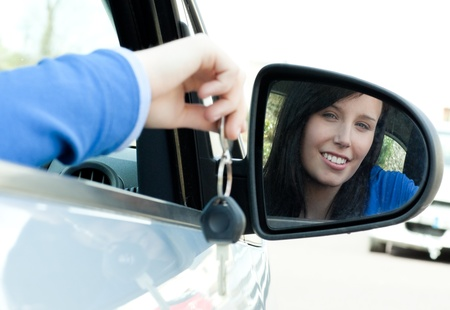 Cheerful teen girl sitting in her car holding keys photo