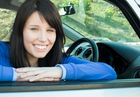 l plate: Happy teen girl smiling at the camera sitting in her car
