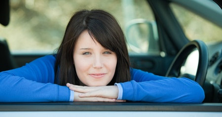 l plate: Cute teen girl smiling at the camera sitting in her car Stock Photo