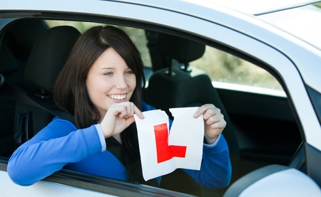 driving school: Joyful teen girl sitting in her car tearing a L-sign  Stock Photo
