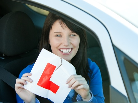 driving school: Smiling brunette teen girl sitting in her car tearing a L-sign  Stock Photo