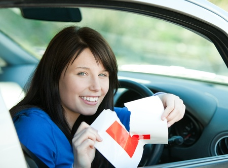 l plate: Charming brunette teen girl sitting in her car tearing a L-sign