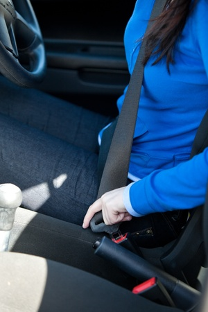 safety: Close-up of caucasian woman putting seat belt