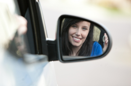 Attractive teen girl sitting in her car holding keys photo