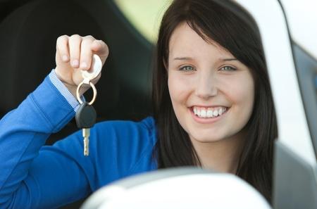 l plate: Brunette teen girl sitting in her car holding keys