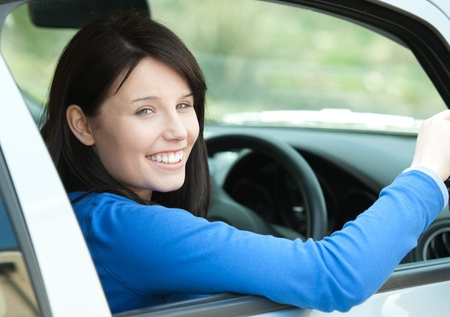 Portrait of a smiling woman driving  photo