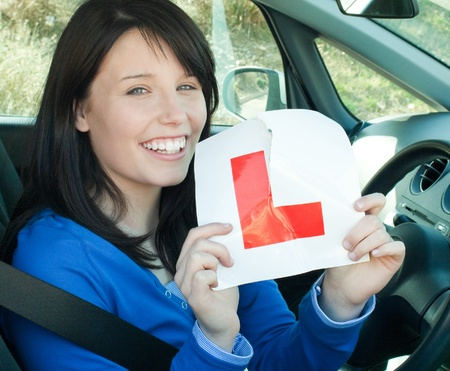 l plate: Happy teen girl sitting in her car tearing a L-sign